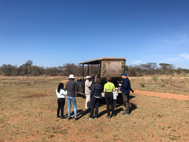 En grupp människor runt en safaribil.