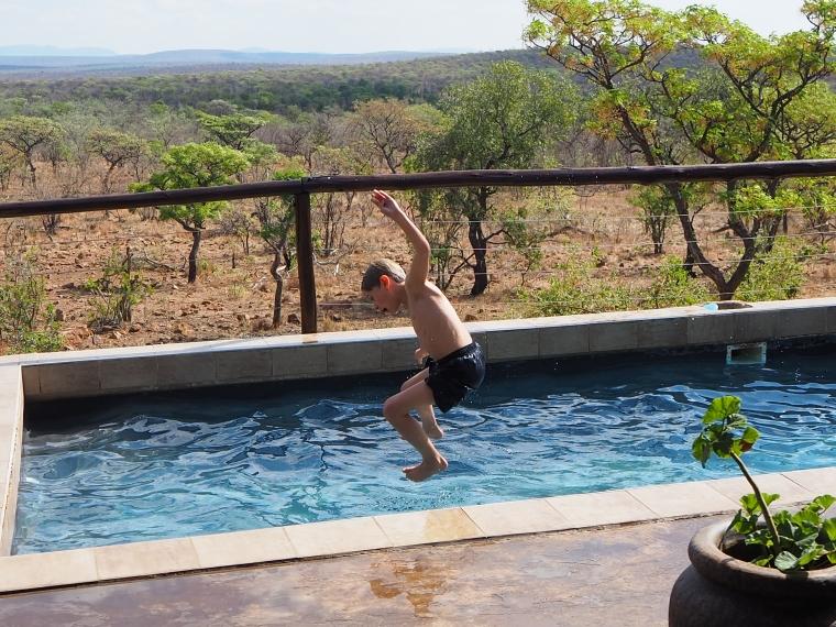Ett barn hoppar ner i en pool.
