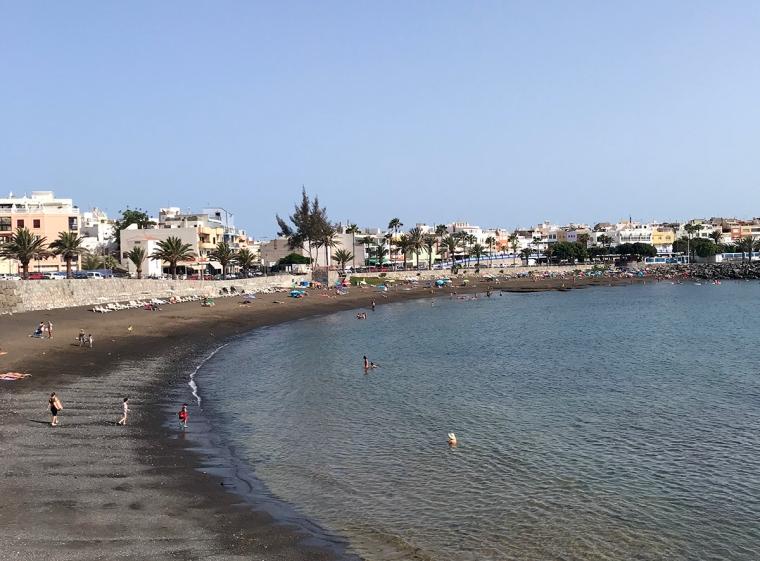 En svart sandstrand och hav.