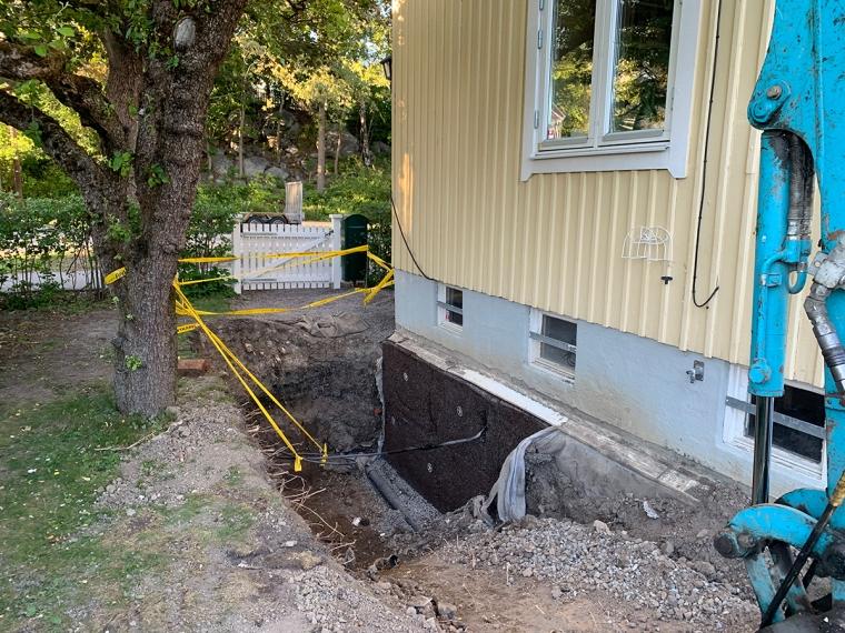 En grop bredvid ett hus där en kabel syns.
