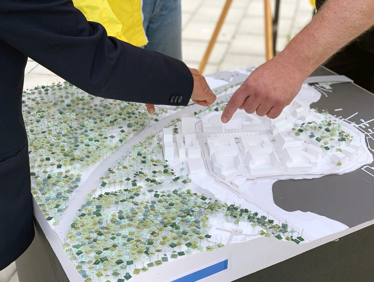 Tre händer pekar på en modell av ett bostadsområde.