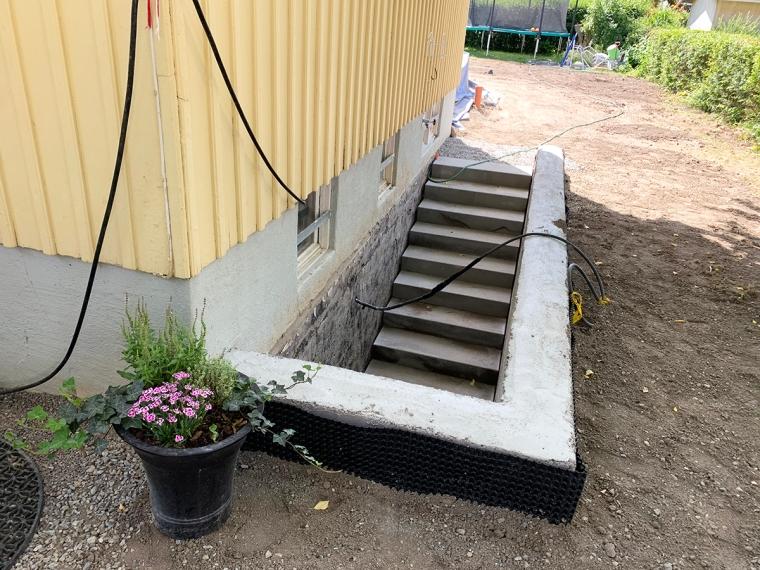 En nybyggd betongtrapp och en trädgård som bara är en leråker.