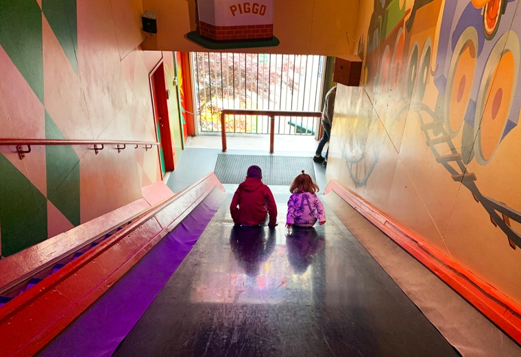 Två barn åker på en rutschkana.