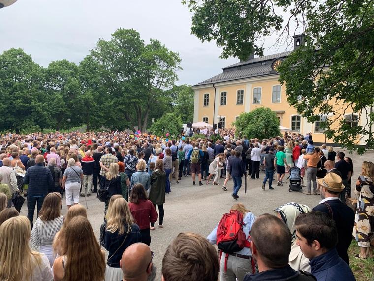 Massa folk utanför en gul gammal byggnad.