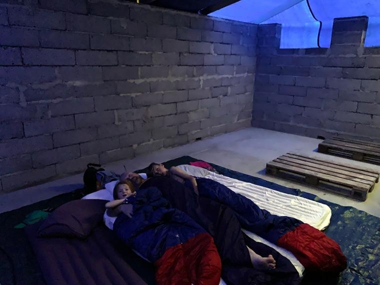 En vuxen och två barn på madrasser på ett betonggolv.
