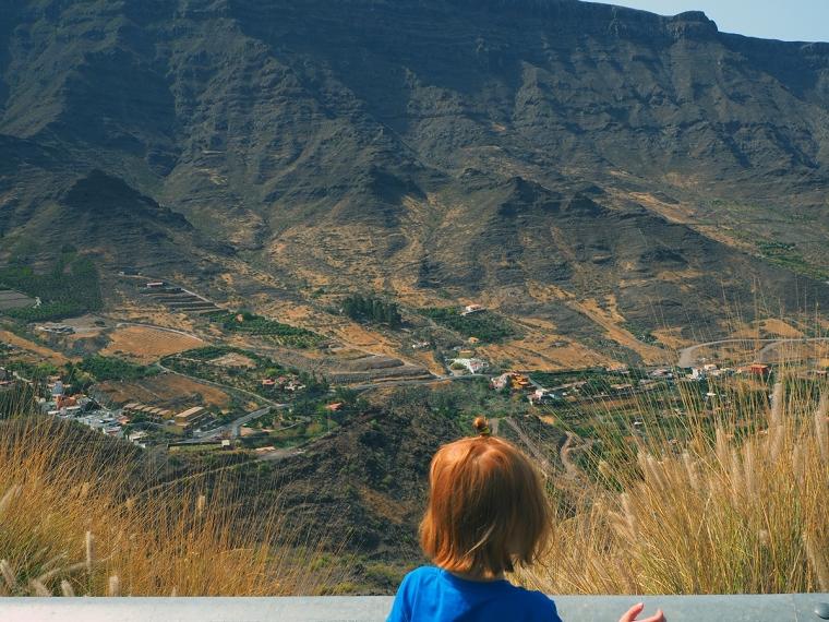 Ett barn tittar ut över berg och dal.