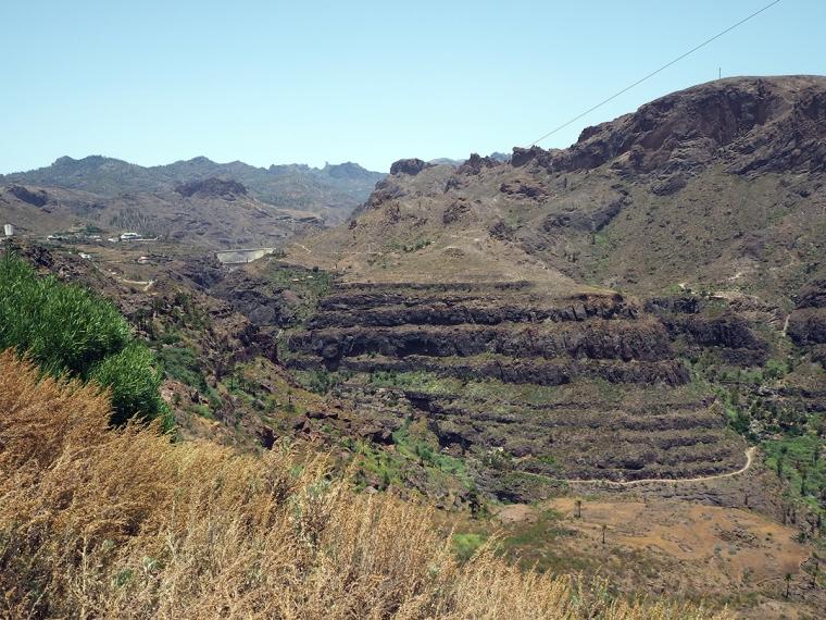 Landskap med höga berg och en grå damm.