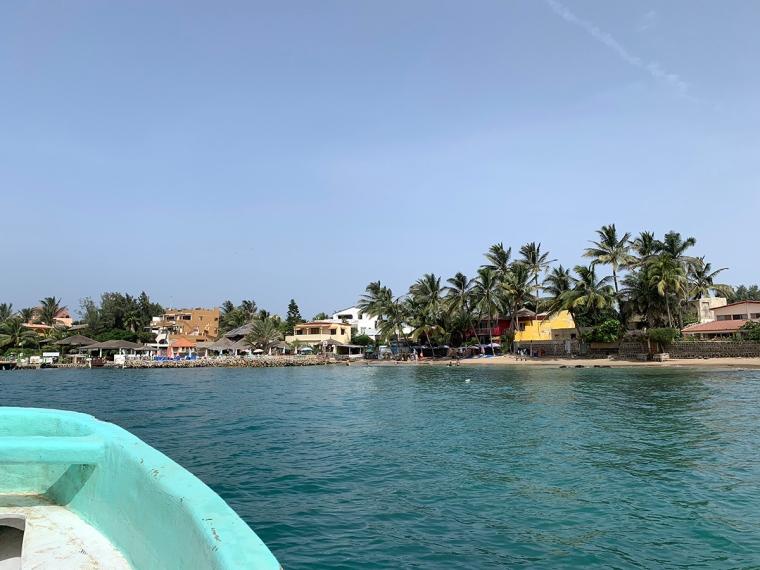 Några hus och palmer på en strand sedda från havet.