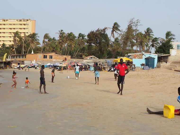 En handfull män spelar fotboll i stranden.