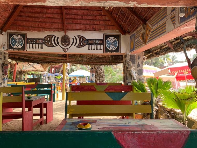 Sandgolv, bänkar och bord i rött, gult och grönt.