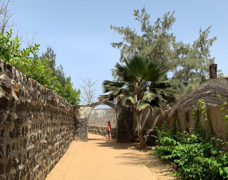 Sandgång omgärdad av murar och grönska.