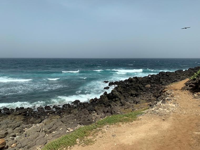 Svarta klippor och mörkblått hav med vita vågor.