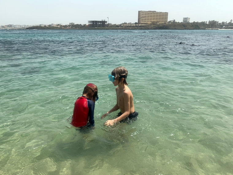 Två barn står i vattnet med masker på.