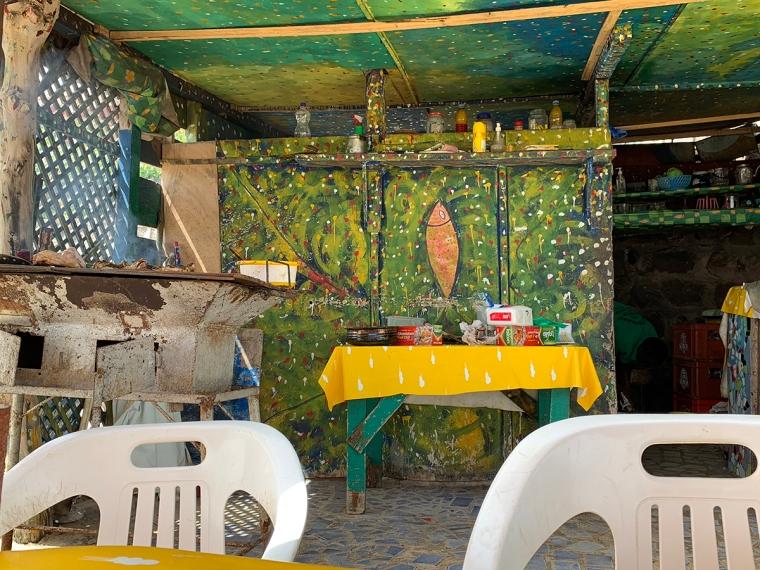 En färgglad restaurang med ett oljefat som grill.