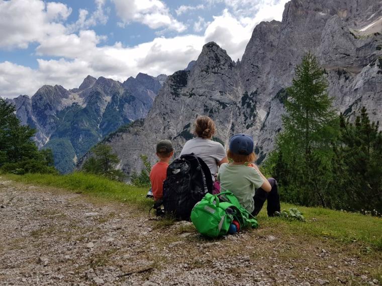 En kvinna och två barn sitter och tittar på utsikt över berg.