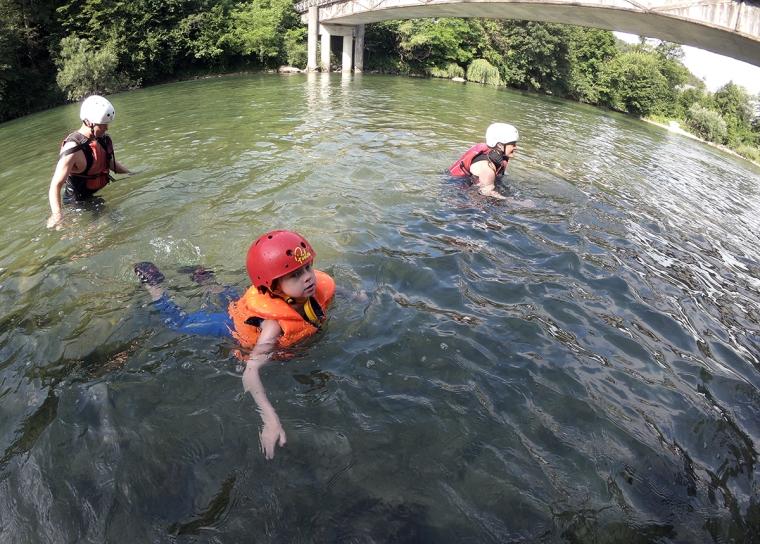 Två vuxna och ett barn simmar iförda hjälm och flytväst.