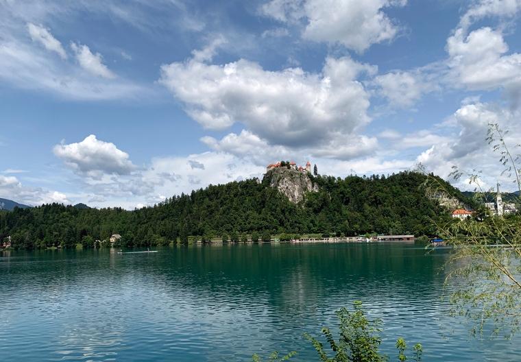 En sjö i förgrunden och ett vitt slott uppe på ett berg.