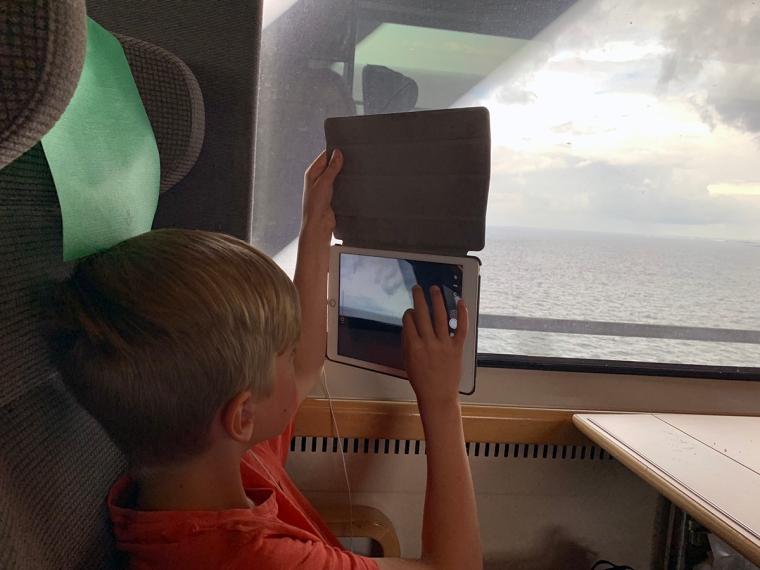 Ett barn på ett tåg tar kort med sin iPad.