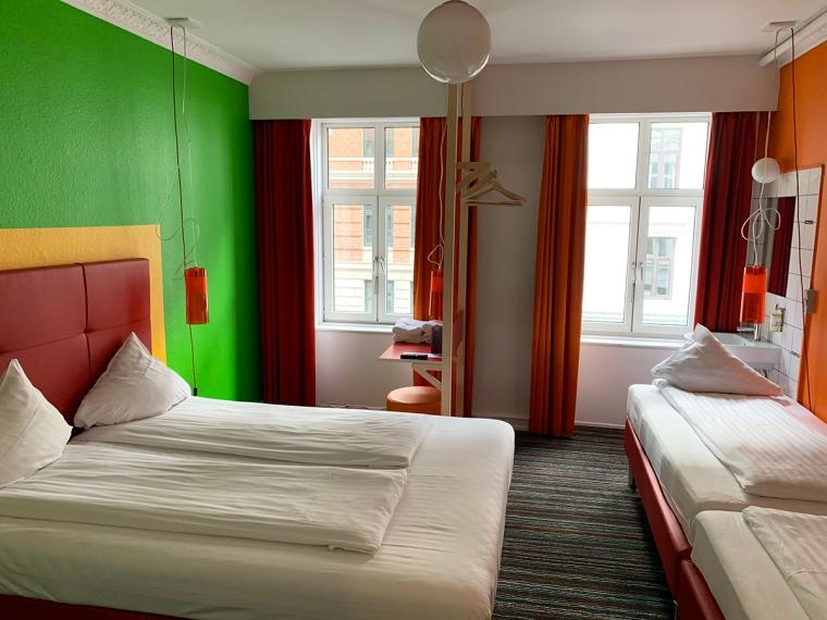 Ett rum med en dubbelsäng och två enkelsängar samt ett skrivord och ett handfat.