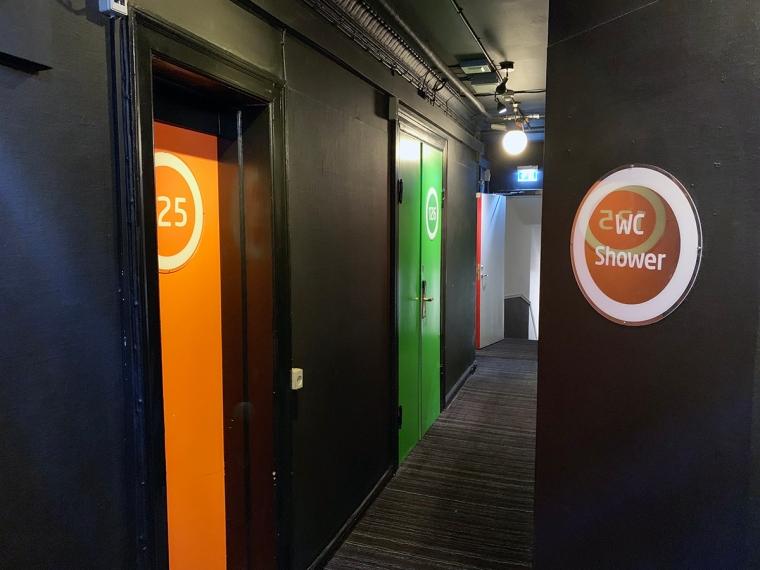 En svart korridor med dörrar i skrikiga färger.