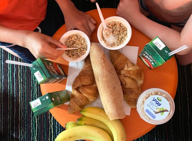 Ett bord med bananer, bröd, jos och yoghurt.