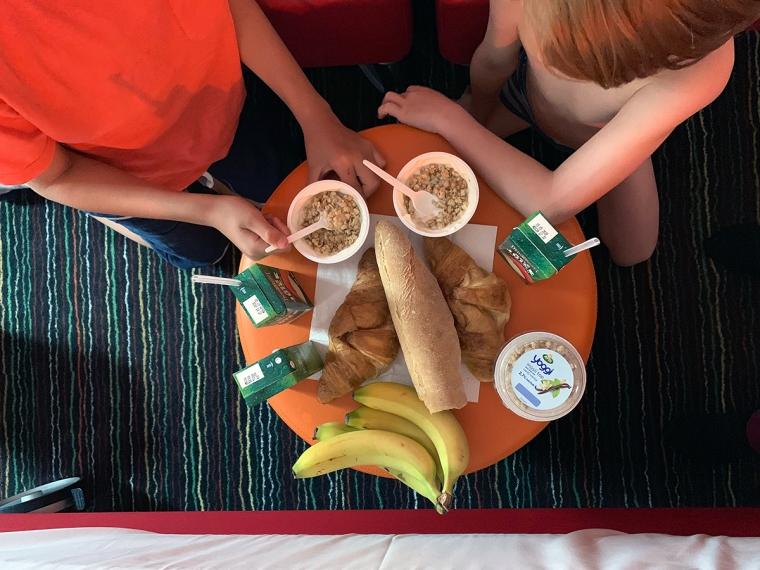 Två barn vid en uppdukad frukost med yoghurt, bröd och frukt.