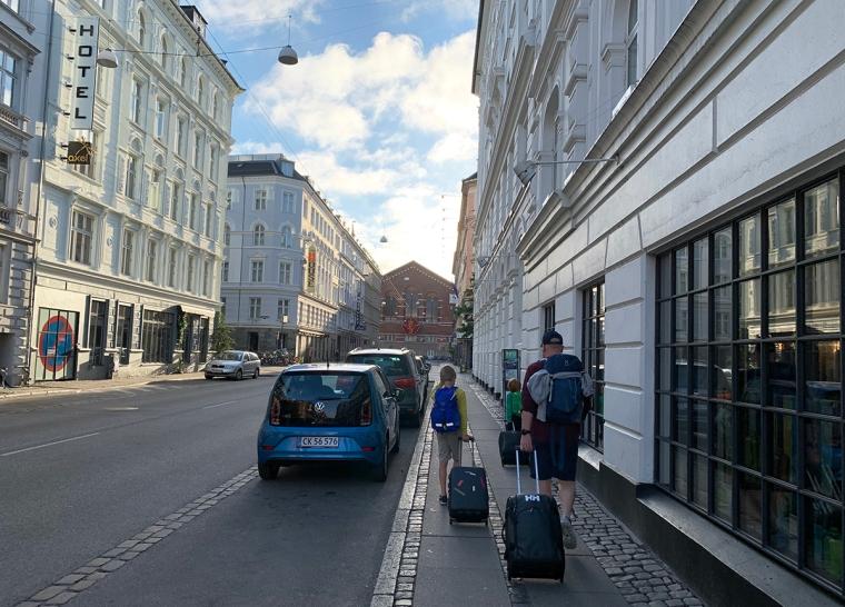 Två barn och en man går med väskor på en gata.