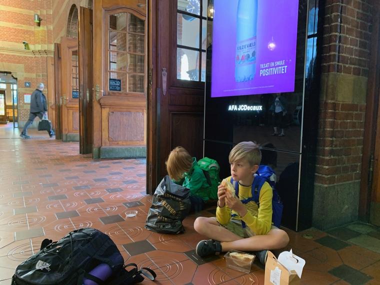 Två barn sitter på ett stationsgolv och äter frukost.