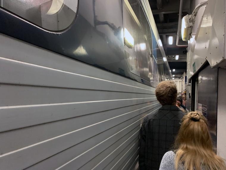 En trång passage mellan ett tåg och en vägg.