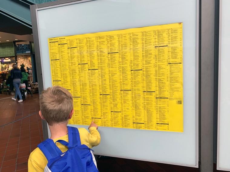 Ett barn står framför en gul skylt med massor av liten svart text.