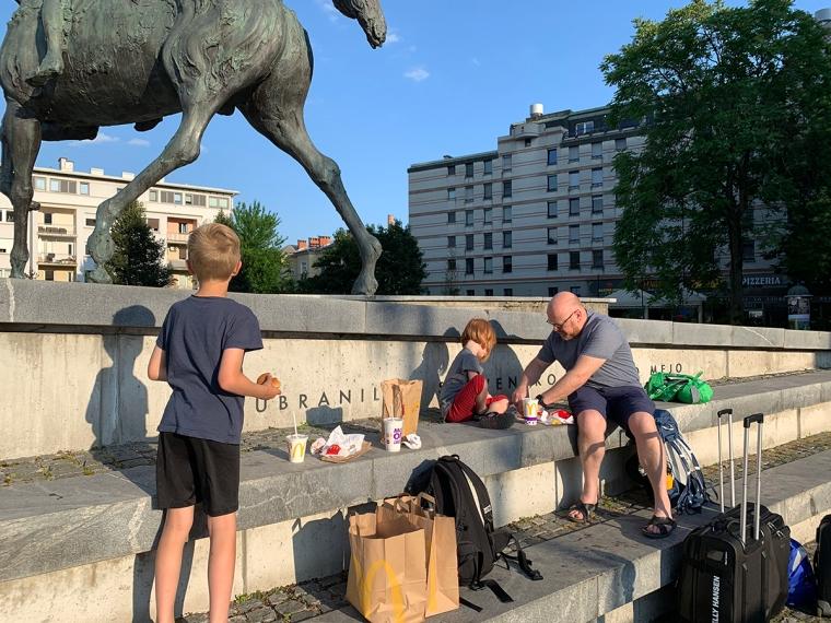 En man och två barn sitter och äter mat från Mc Donlads vid en staty.