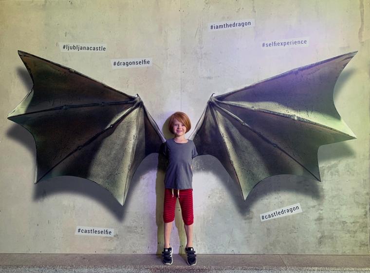 Ett barn som står framför ett par drakvingar.