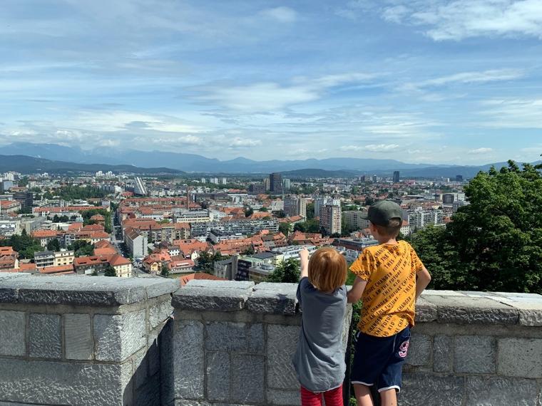 Två barn står i förgrunden och blickar ut över staden.