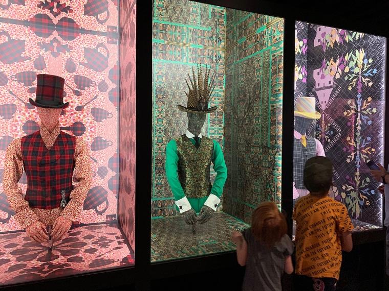 Två barn tittar på designade kläder.