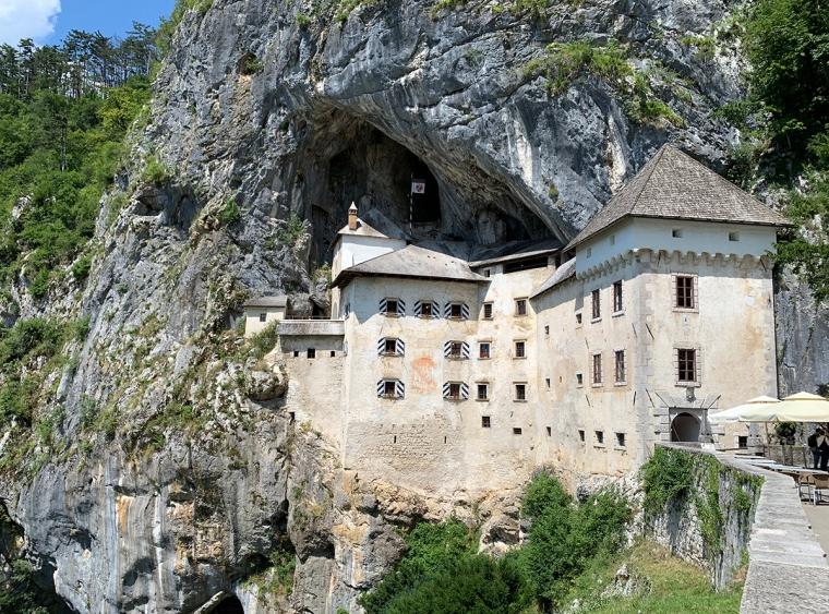 Ett vitt slott som hänger på ern bergvägg.