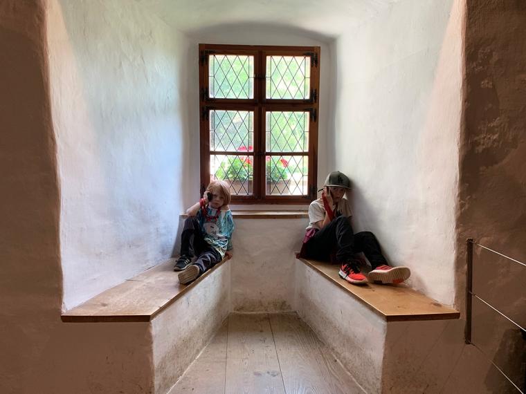 Två barn sitter på var sin bänk och lyssnar i en radio.