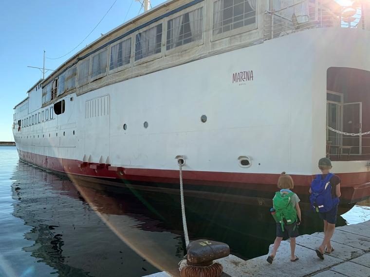 Två barn utanför en stor vit båt.