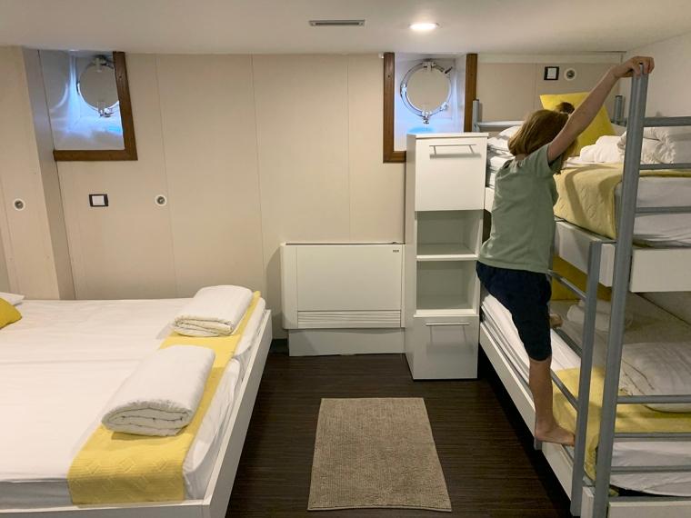 En hytt med en dubbelsäng och en våningssäng. Kuddar och filtar är gula.