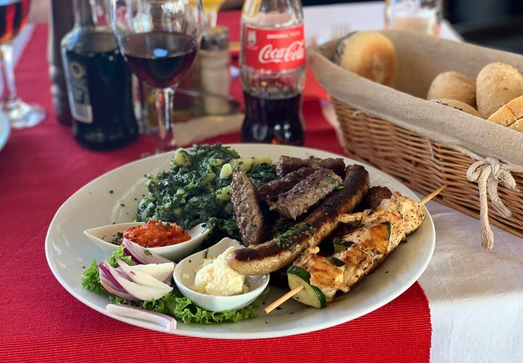 En tallrik med blandat grillat kött, två såser och potatis med mangold.