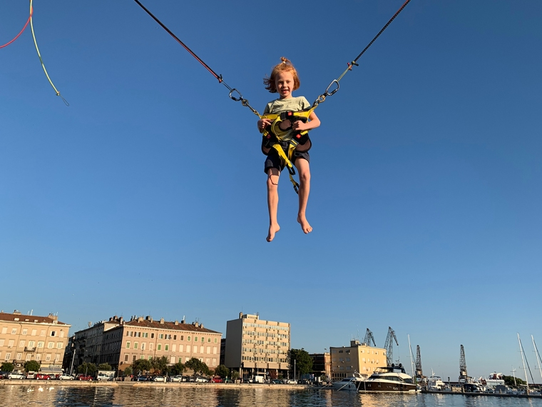 Ett barn med sele som hoppar på en suddsmatta.