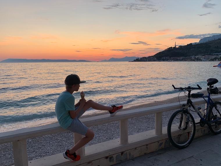 Ett barn sitter vid havet och äter glass i solnedgång.