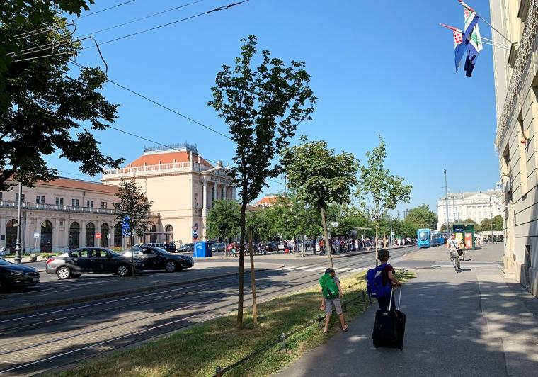 Två barn med väskor går på en gata med en tågstation i bakgrunden.