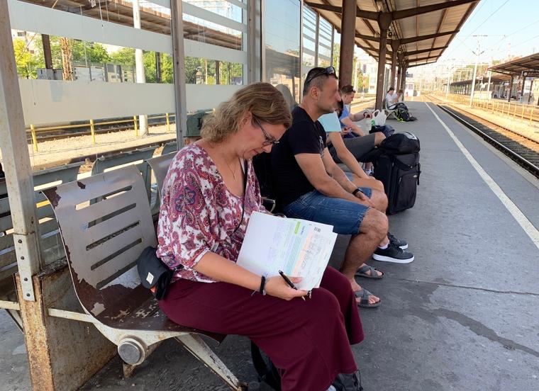 En kvinna sitter på en bänk på en tågperrong och fyller i papper.