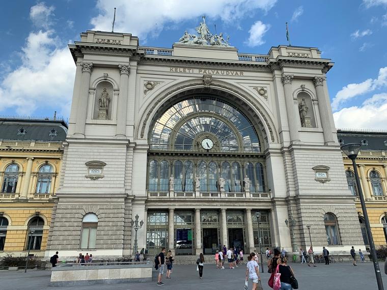 Fasade på en station. Grå, hög, glaspartier och statyer.
