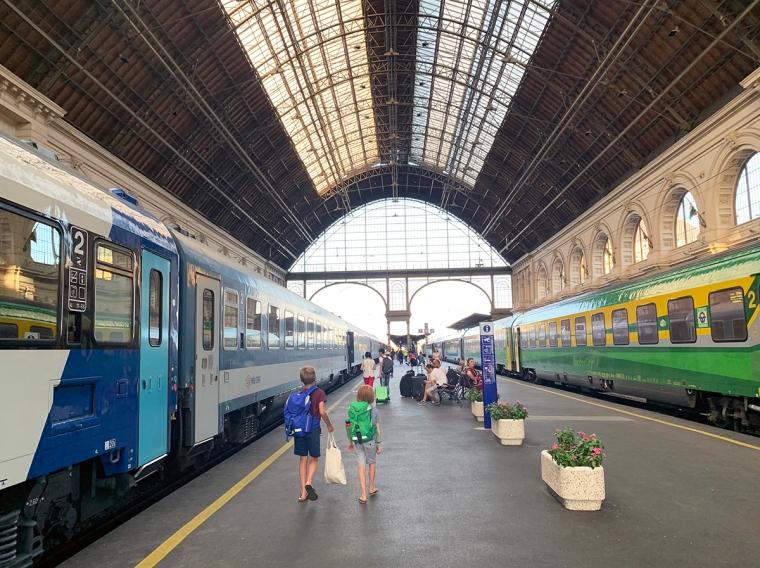Två barn på en perrong med två tåg inne.