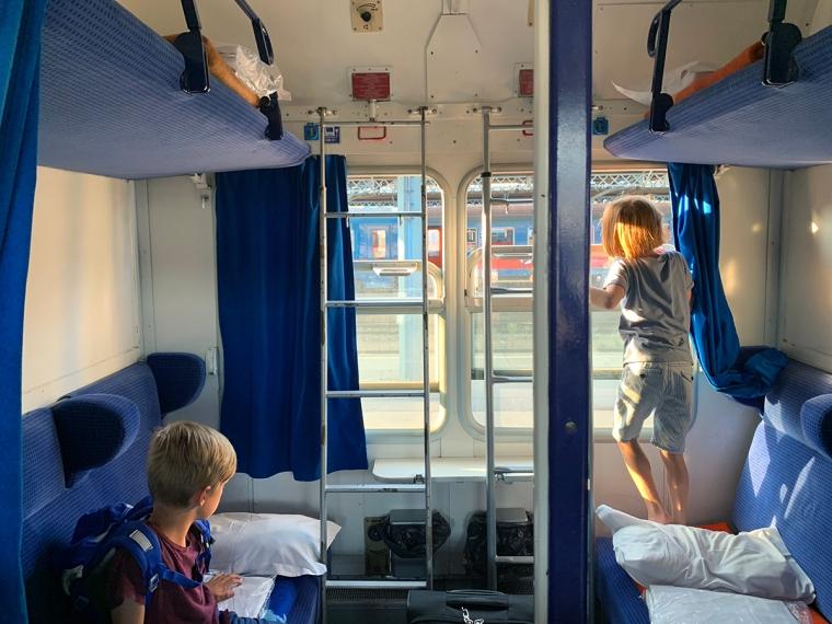 Två barn i en tågkupé med två slafar under taket och två soffor längs sidorna. Allt blått utom de vita väggarna.