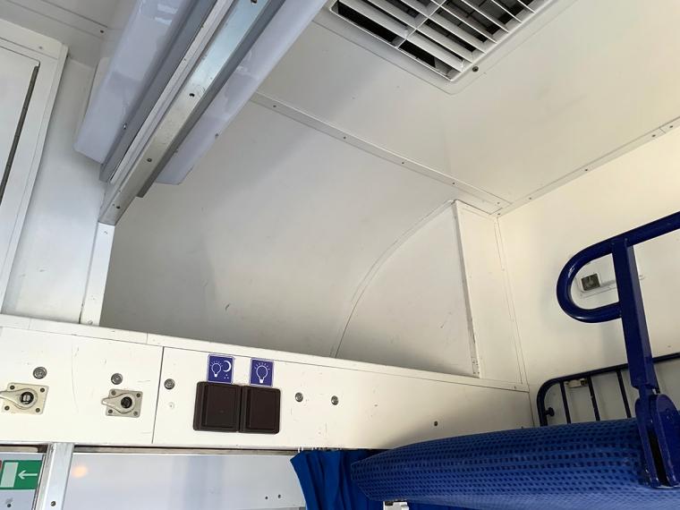 Ett utrymme till förvaring bredvid en överslaf på ett tåg.