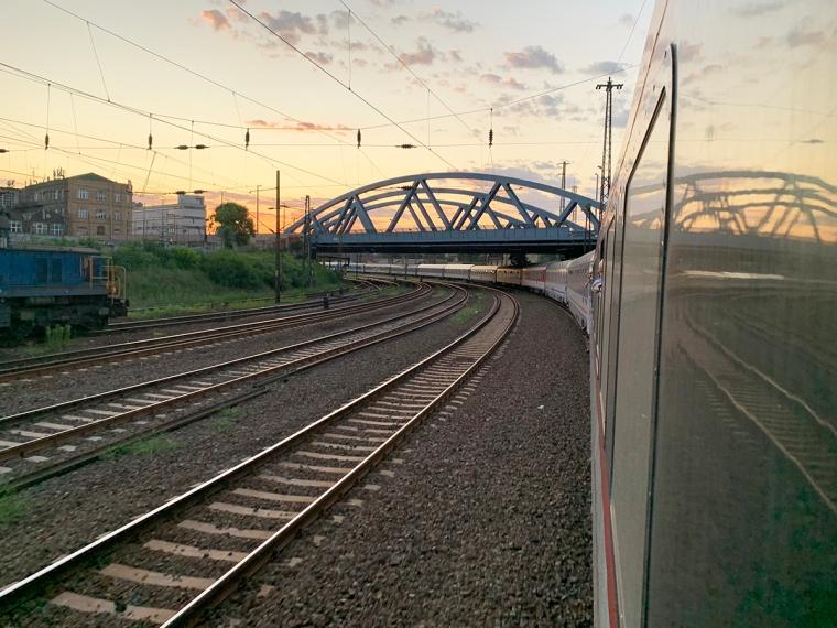 Ett tåg i en kurva som passer under en bro med solnedgång på himlen.