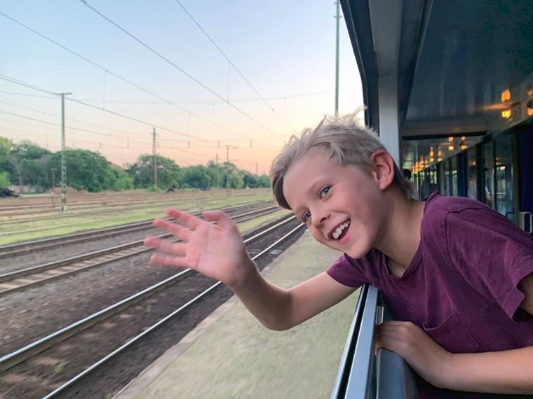 Ett barn lutar sig ut genom ett tågfönster och vinkar.