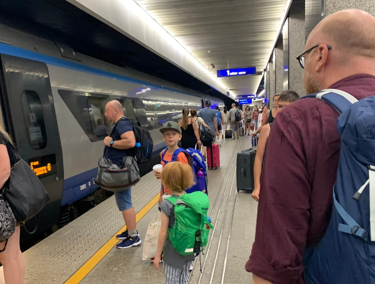 Två barn står på en perrong och ett tåg har kommit in.